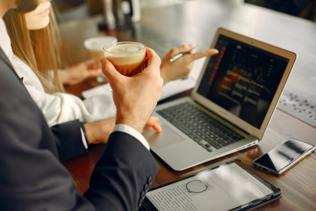 man working on laptop with coffee in hand